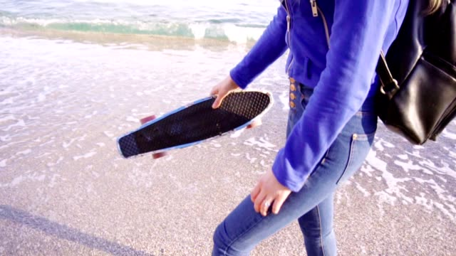 Blonde woman with long hair walks by the sea with skate video
