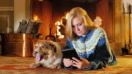 Blonde young woman reading e-book reader against the background of a burning fireplace. Next to it is a large dog video
