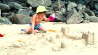 blonder bub spielt mit sand auf einem strand in thailand video