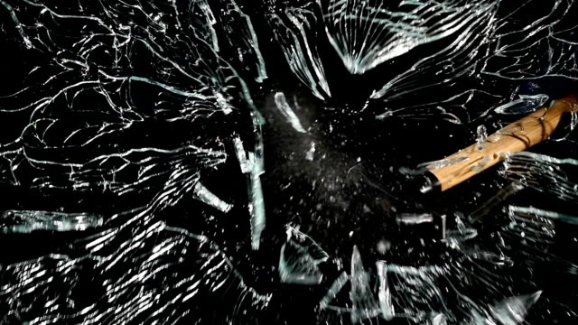 Blow to the glass with a hammer crumbles into fragments. Black background. Slow motion video
