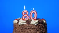 Blowing out number eighty birthday candles on a delicious chocolate cake, blue screen video
