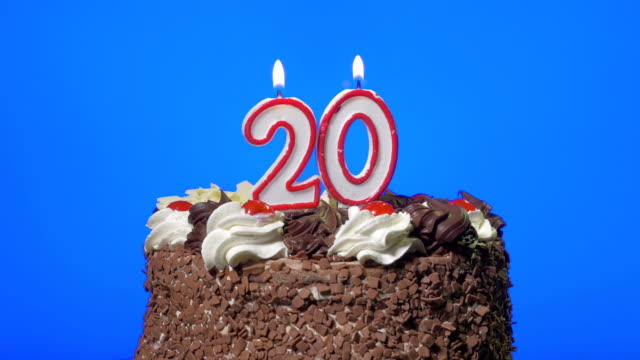 Blowing out number twenty birthday candles on a delicious chocolate cake, blue screen video