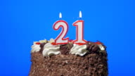 Blowing out number twenty-one birthday candles on a delicious chocolate cake, blue screen video