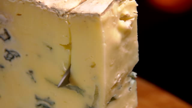Blue cheese cut on the background of a burning fireplace video