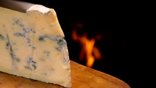 Blue cheese cut on the background of a fireplace video