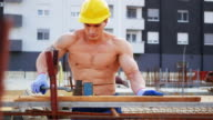 Blue collar worker on construction site, banding armature video