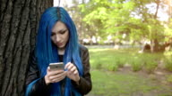 Blue haired girl using smartphone video