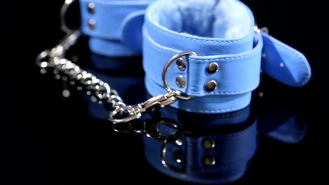 blue leather handcuffs in black background. sex toy video