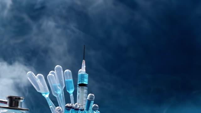 Blue liquid in glass tube test lab, dropper, syringe, blur helmet, stethoscope, glove and goggle eyewear, tube rotating on device machine video