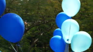 Blue party balloons floating at outdoor terrace, fun and bright day for celebration video