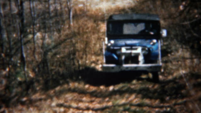 1962: Blue soft-top jeep driving thru forest offroad trail. video