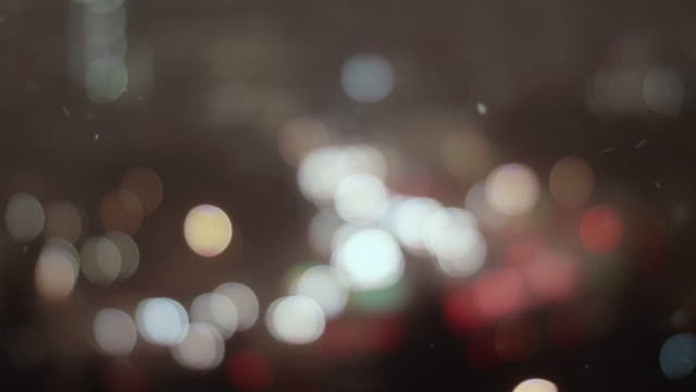 Blur Background of City Lights Bokeh with Snow Flakes Falling in Focus video