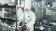 Blur footage of three professional chefs in a commercial kitchen in a restaurant or hotel preparing food. video