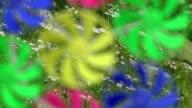 Blurred background of rainbow windmills turning video