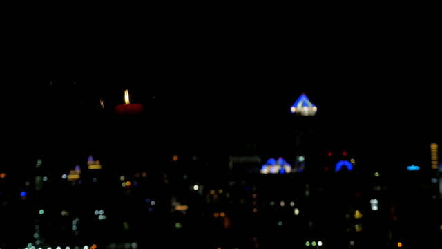Blurred city lights and candle reflection in the window video
