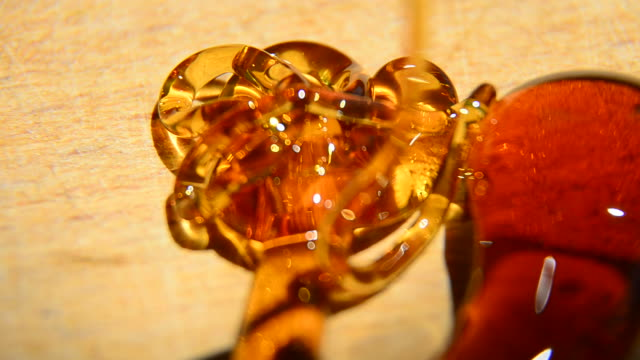 Blurred motion of honey flowing, forming abstract forms, Extreme closeup video