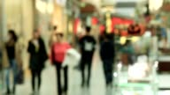 Blurred people in motion, people walking in shopping center, out of focus movie shot video