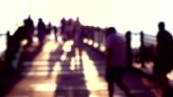 Blurred people on sunny park arched bridge. Super slow motion shot, purple colors. 240 fps video