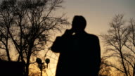 Blurred silhouette of business man in coat talking at smartphone and making deals on street with sunlight backlit in evening time video
