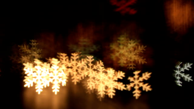 Blurring lights bokeh background of snowflakes video