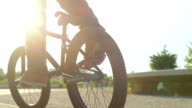 SLOW MOTION CLOSEUP: Bmx biker pedaling and jumping 360 rotation trick on street video