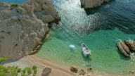 AERIAL Boat anchored in bay by a wild beach video