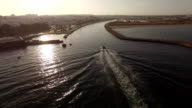 Boat comes into the harbor at sunset aerial view video