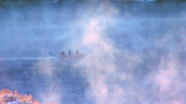 Boat crossing lake with snow and fog rising in foreground video
