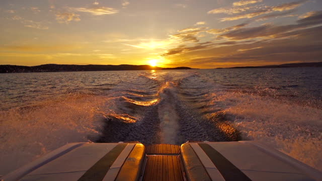 Boat driving away from sunset video