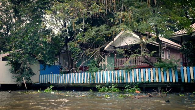 Boat POV Passing Riverside Houses In Tropical Landscape video