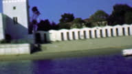 1958: Boat traveling upriver passing art deco style utilities building. video