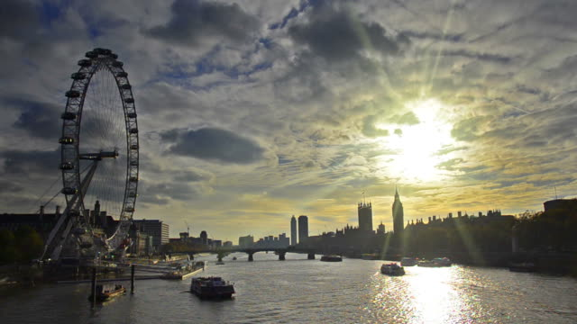 Boats passing along Thames river with sunset silhouette London skyline video