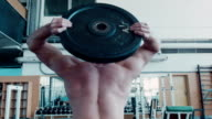 Bodybuilder does rotating exercise with barbell video