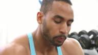 Bodybuilder drinking a protein shake at a gym video