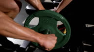 bodybuilder puts weight on the barbell. Communicates with a pretty athlete video