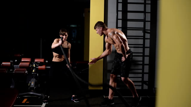 bodybuilder teaches exercise his girlfriend. Athletic young woman doing some gym exercises with a rope video