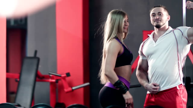 Bodybuilding couple posing looking in the gym mirror video