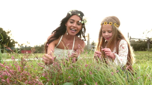 Boho chic woman and little girl picking tiny flowers video
