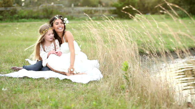 Boho chic woman and little girl sitting by water video