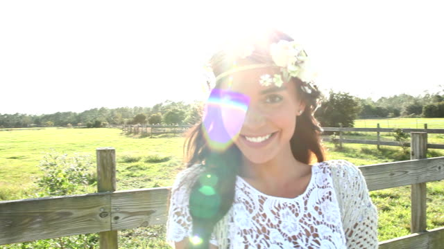 Boho chic woman standing by wood fence and pasture video