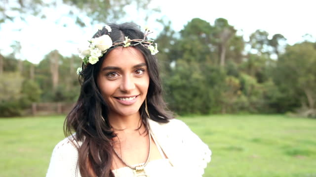 Boho chic woman standing in a field smiling at camera video