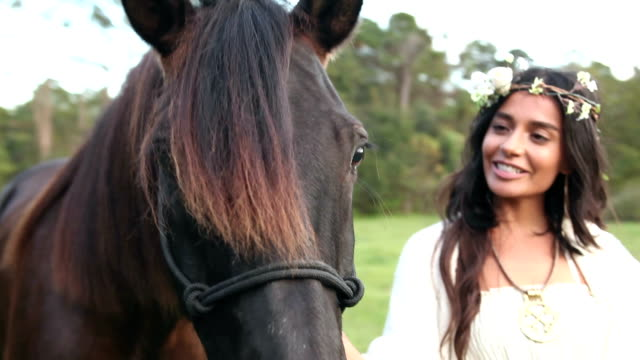 Boho chic woman standing with chestnut brown horse video