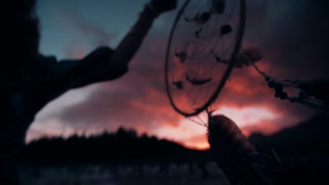 Boho girl holding up a dream catcher on summer evening video