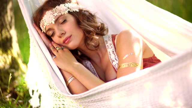 Boho girl sleeping in a hammock in the park video