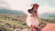 Boho girl walking on a dirt road in summer video