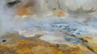 boiling mud pots of geothermal area Krysuvik in Iceland, ground is colored in bright colors video