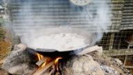 Boiling pork in pan by burning firewood in stove video