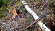 Boiling water in pots above the fire in outdoor. Hunter shotgun video