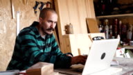 Bold with moustache young Carpenter Craftsman do drawing with laptop in his wooden workshop video