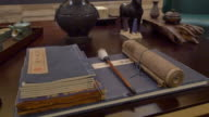 books and Chinese calligraphy tools on table in modern study 4k video